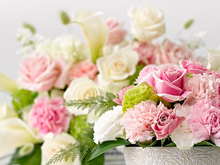 淡いピンクのバラとカーネーションのアレンジメントの画像