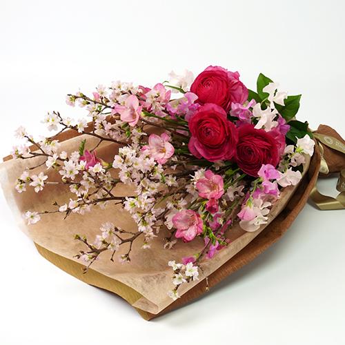 桜とラナンキュラスのロングスタイルの花束の画像