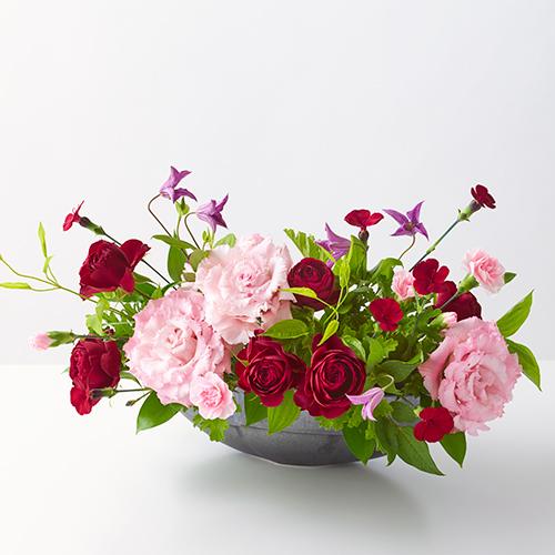 ピンクのトルコキキョウと赤いバラのアレンジメントの画像