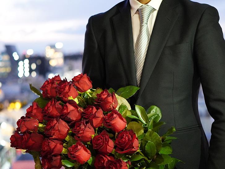赤バラの花束を持った男性の画像