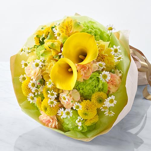 ピンクのスタンド花黄色いカラーを使った花束の画像