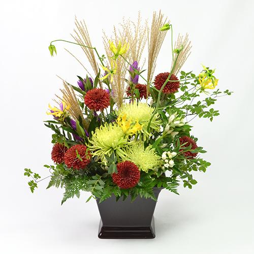ライトグリーンや深い赤色の菊(マム)を使ったアレンジメント
